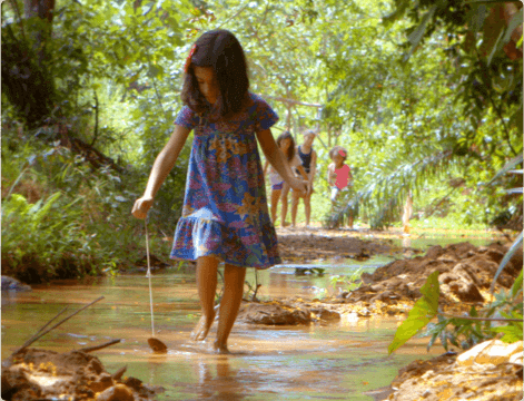 Menina em meio a natureza brincando com uma folha de árvore enquanto atravessa uma poça de água