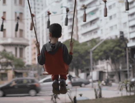 Menino sentado no balanço em um centro urbano