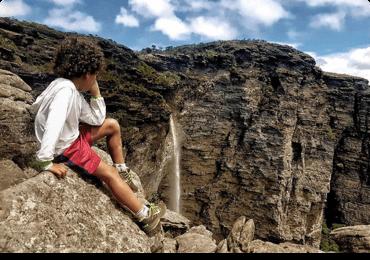 Criança sentada no topo da pedra admirando a natureza